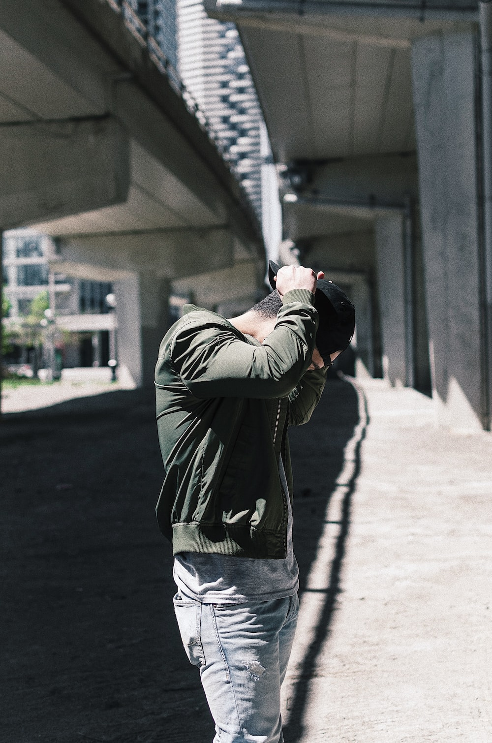 man in green jacket under overpass during daytime