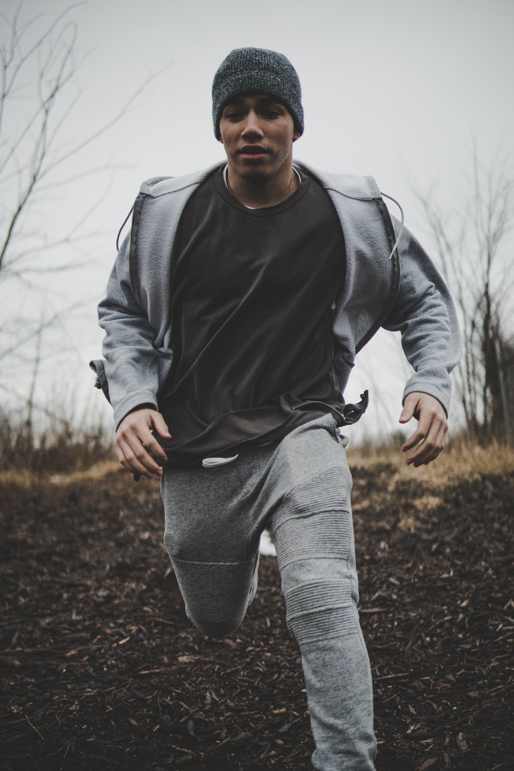 man wearing black shirt and gray jacket with pants while running into plain field