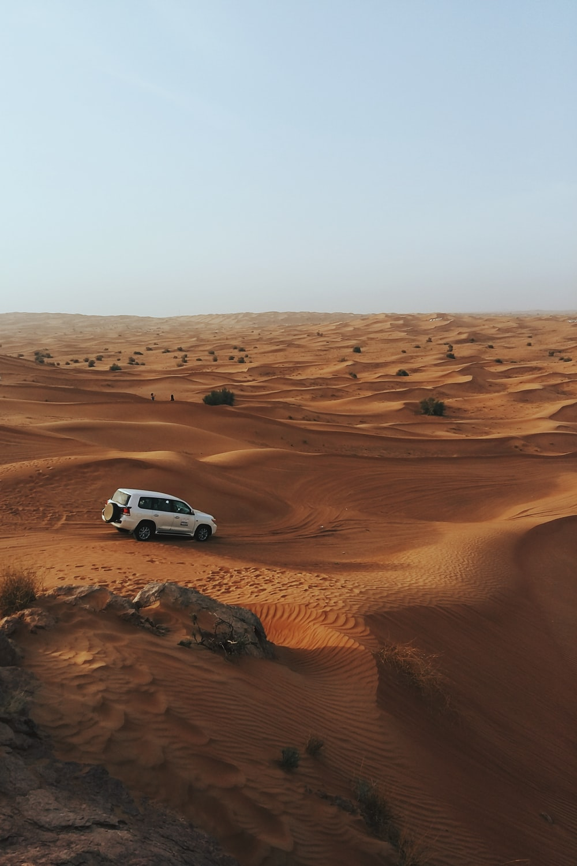 photography of white SUV on desert