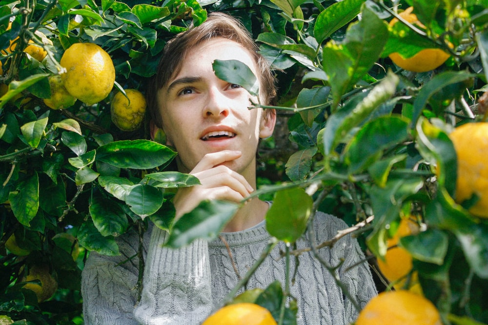 man holding his jaw surrounded by yellow fruit