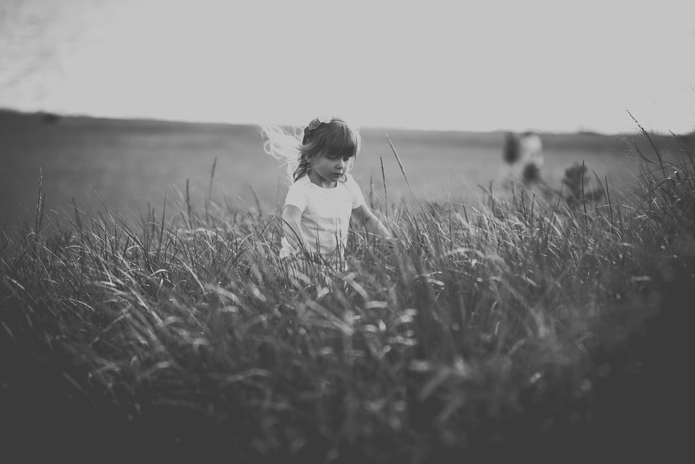 grayscale photography of girl standing on grass field