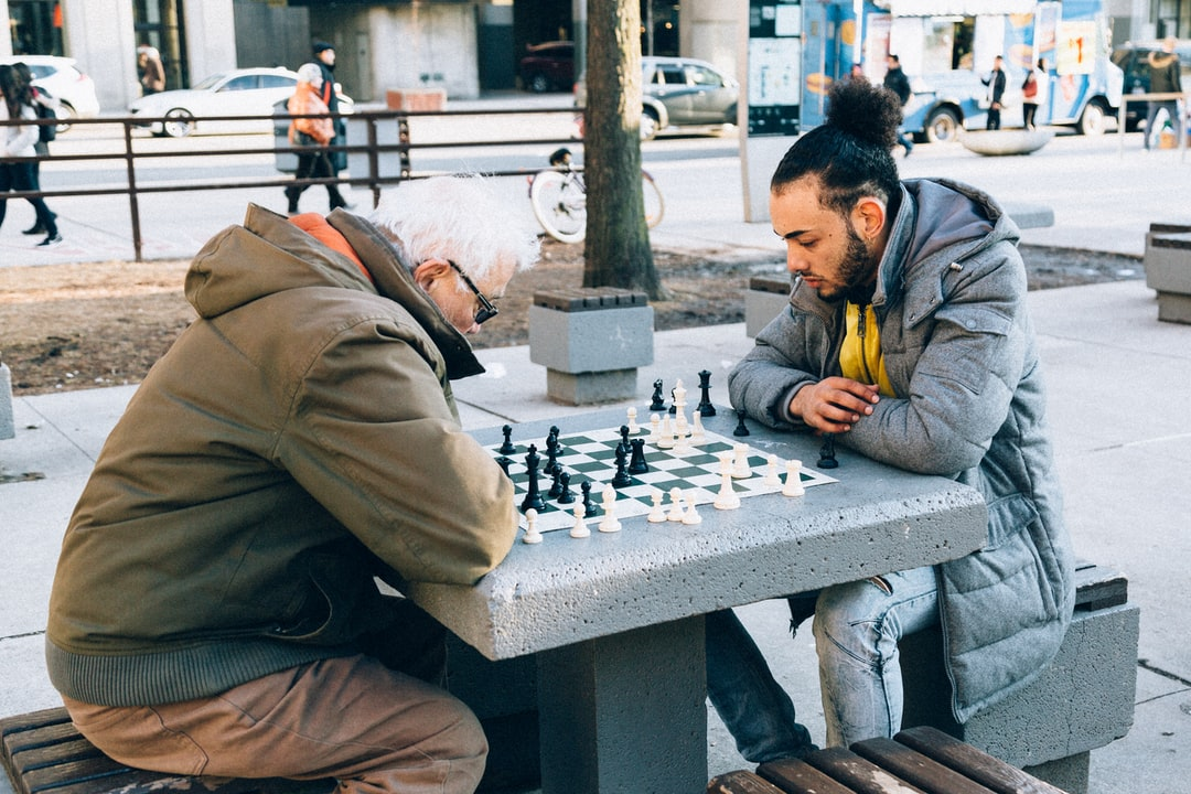 """Went on a photo walk with fellow photographer Naveen (instagram.com/wheresnav) when we came across these two gentleman playing chess. It was a really cold winter day in Toronto and these two didn't mind at all. They were at war. The older gentleman on the left is homeless and lives in a world that is completely different than the one on the right knows, hence  a """"War of the Worlds"""". The strange thing is, even though they are at war, I feel a sense of humanity looking at this photo. There is a human connection, a bond being made between two men from different worlds over a casual game of chess."""