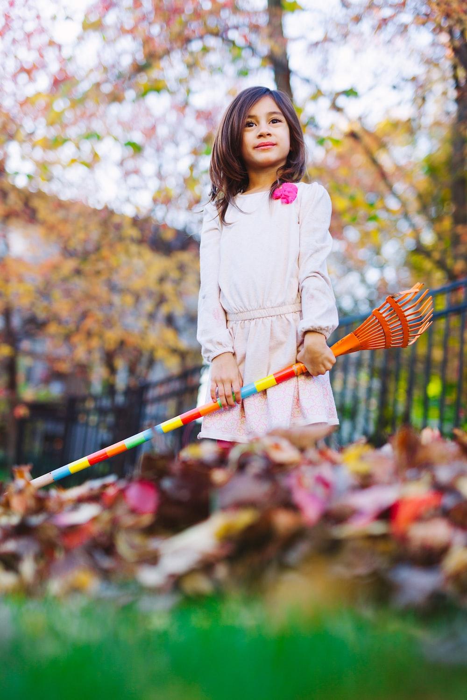 tilt shift photography of girl holding brown wooden rake