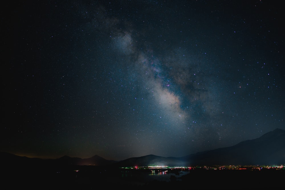 photo of milky way under lighted high-rise buildings