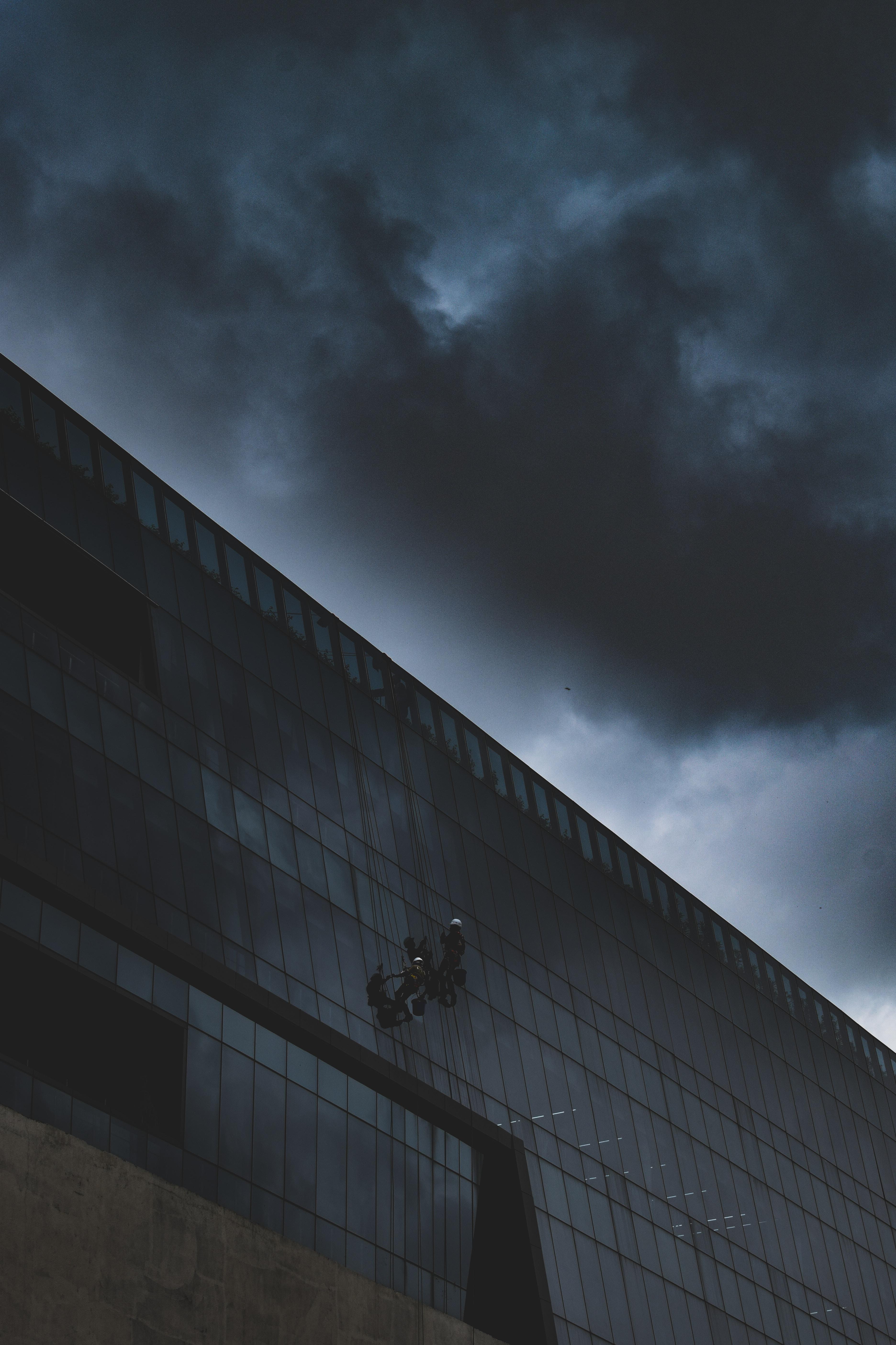 people on building under gloomy sky