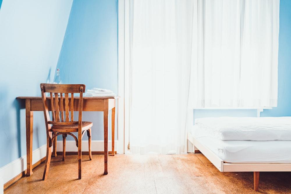 brown wooden chair near mattress