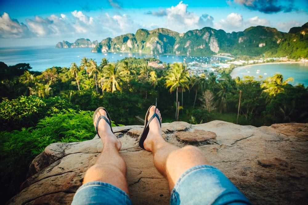 person wearing black flip-flops sitting on rock