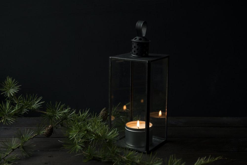 lighted candle inside black lantern holder