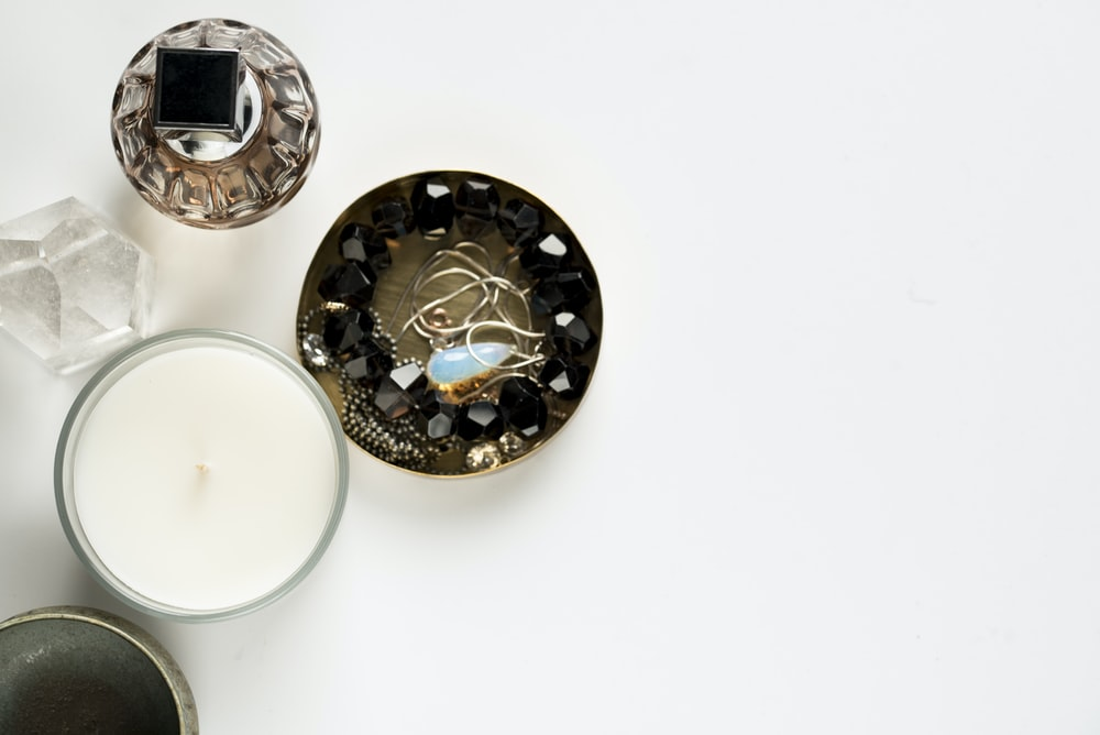 four assorted container and candle on white surface