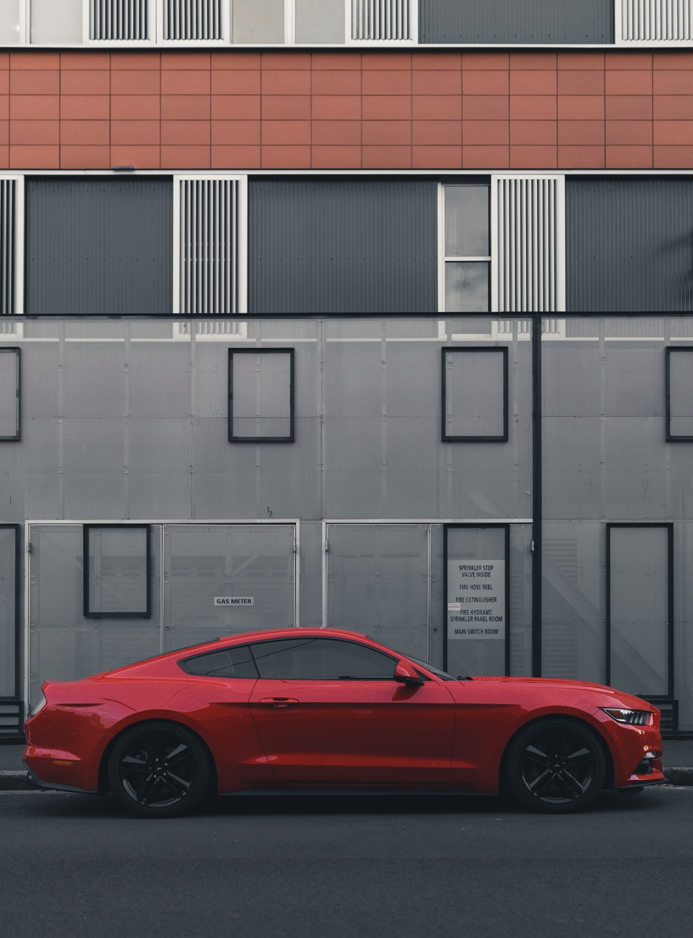 red Ford Mustang coupe parked beside the building