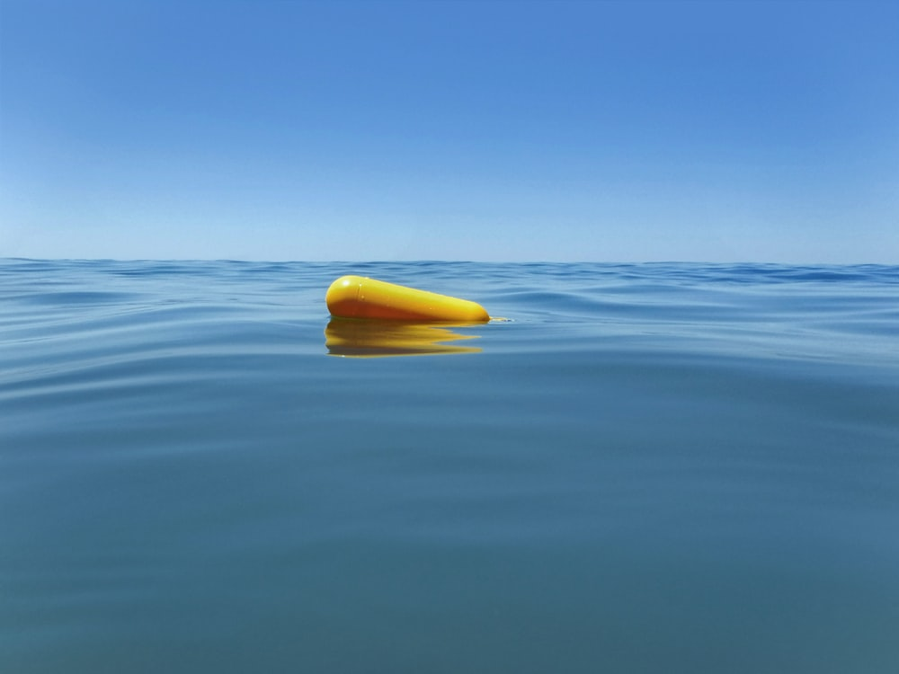 yellow inflatable toy on body of water