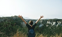 person hands up in front of mountain