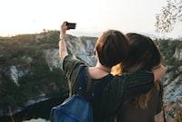 two women taking photo near mountain