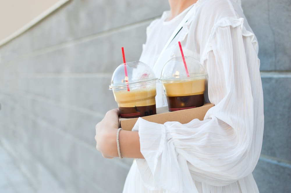 woman carrying disposable cups