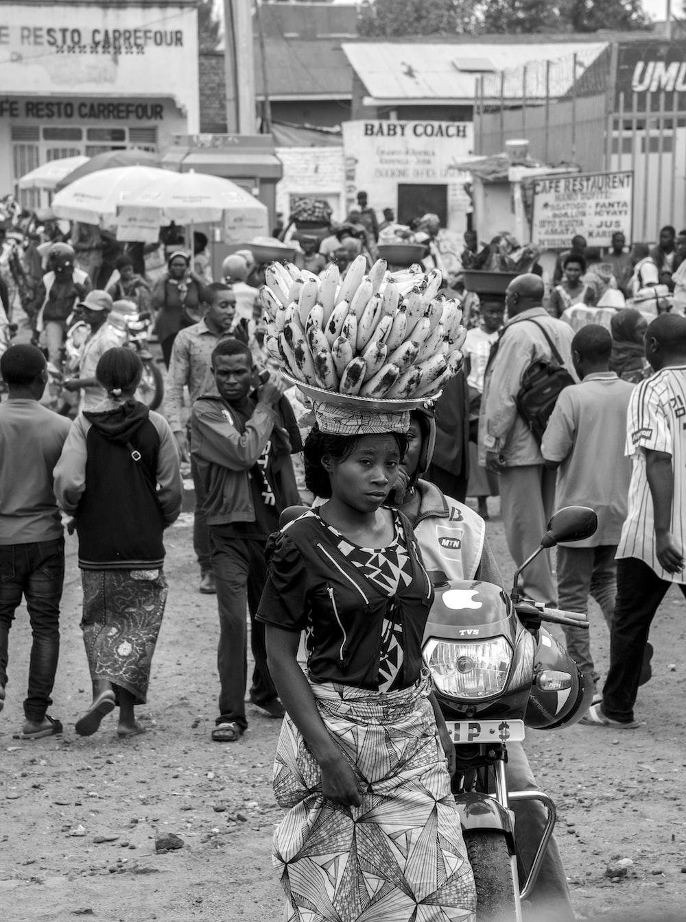 woman carrying bunch of banana on head walking near motorcycle