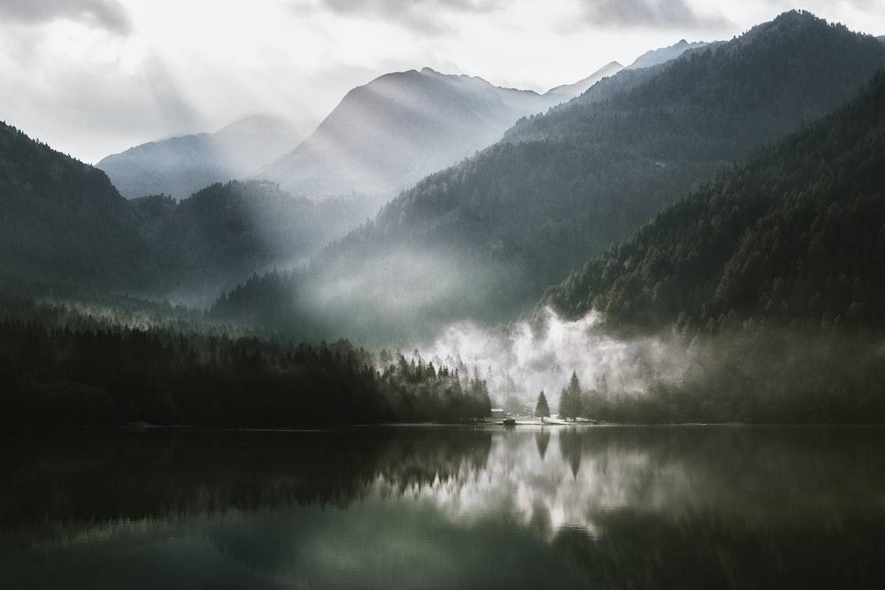 mountain across lake under white sky
