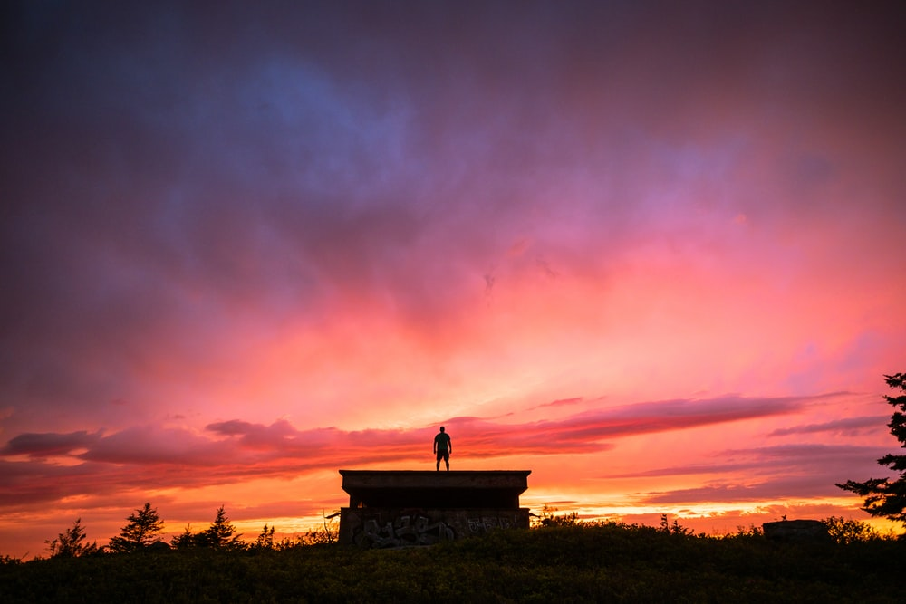 silhouette of person standing on the roof of the house