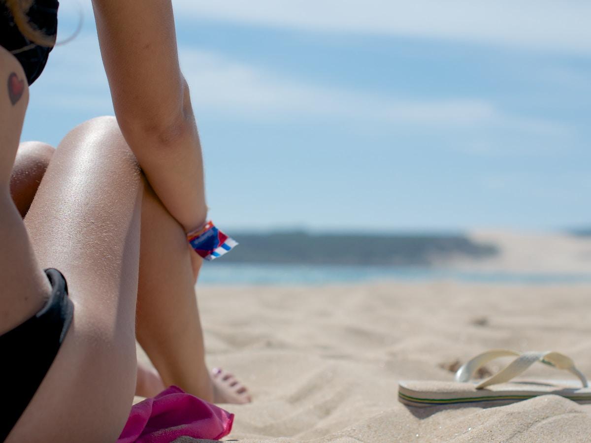 woman sitting on sand beside flip-flop