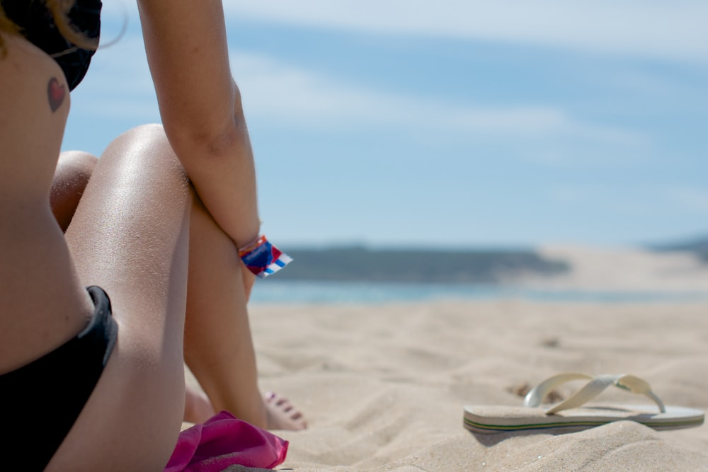 woman sitting on sand beside flip-flop