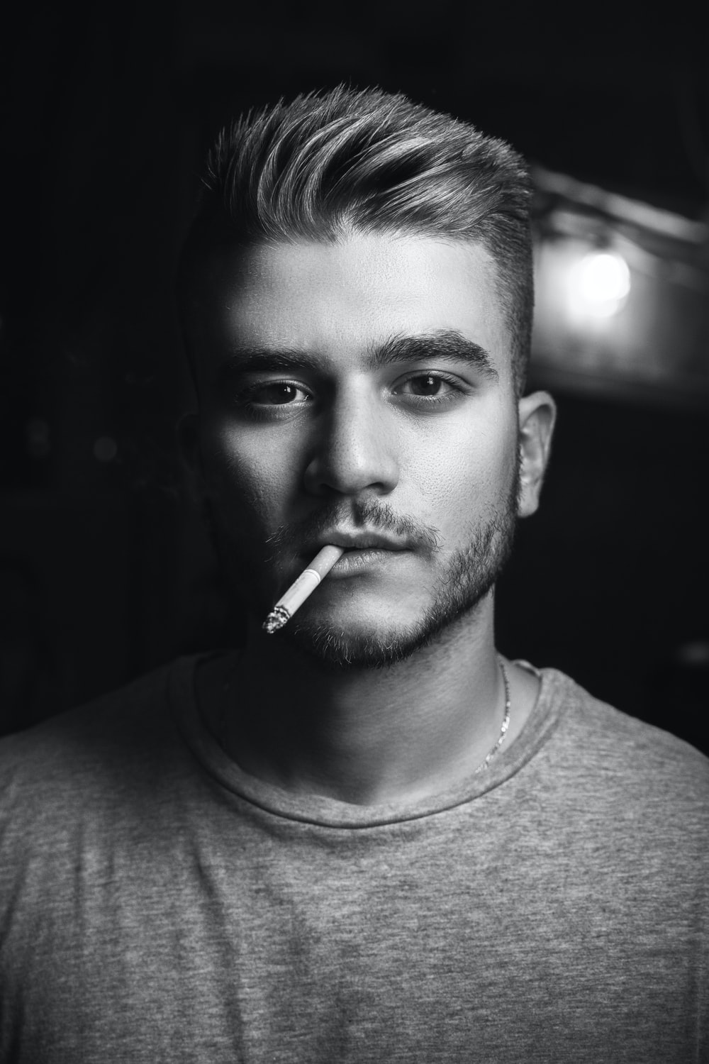 grayscale photography of man smoking while taking picture