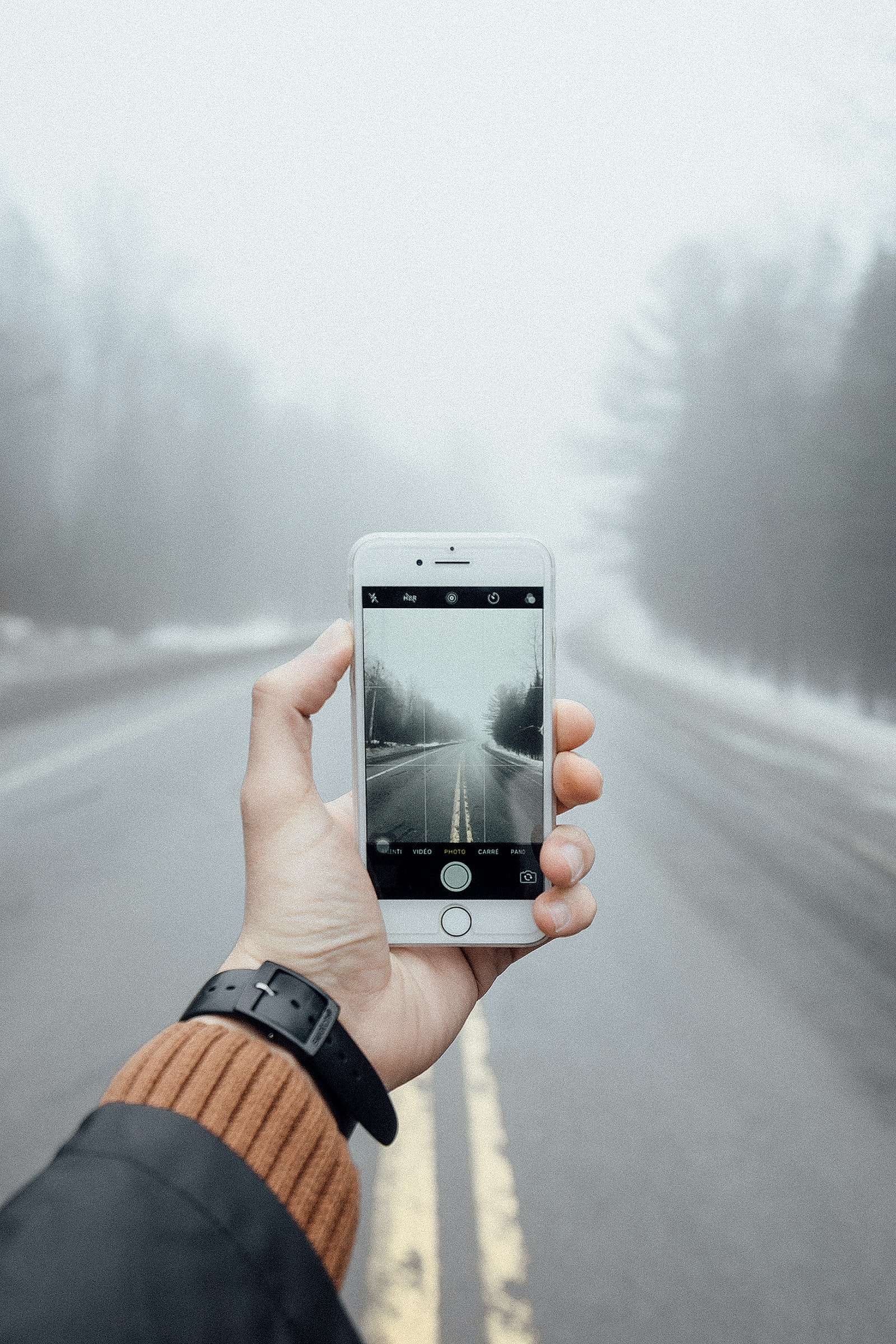person taking photo of foggy asphalt road using silver iPhone 6
