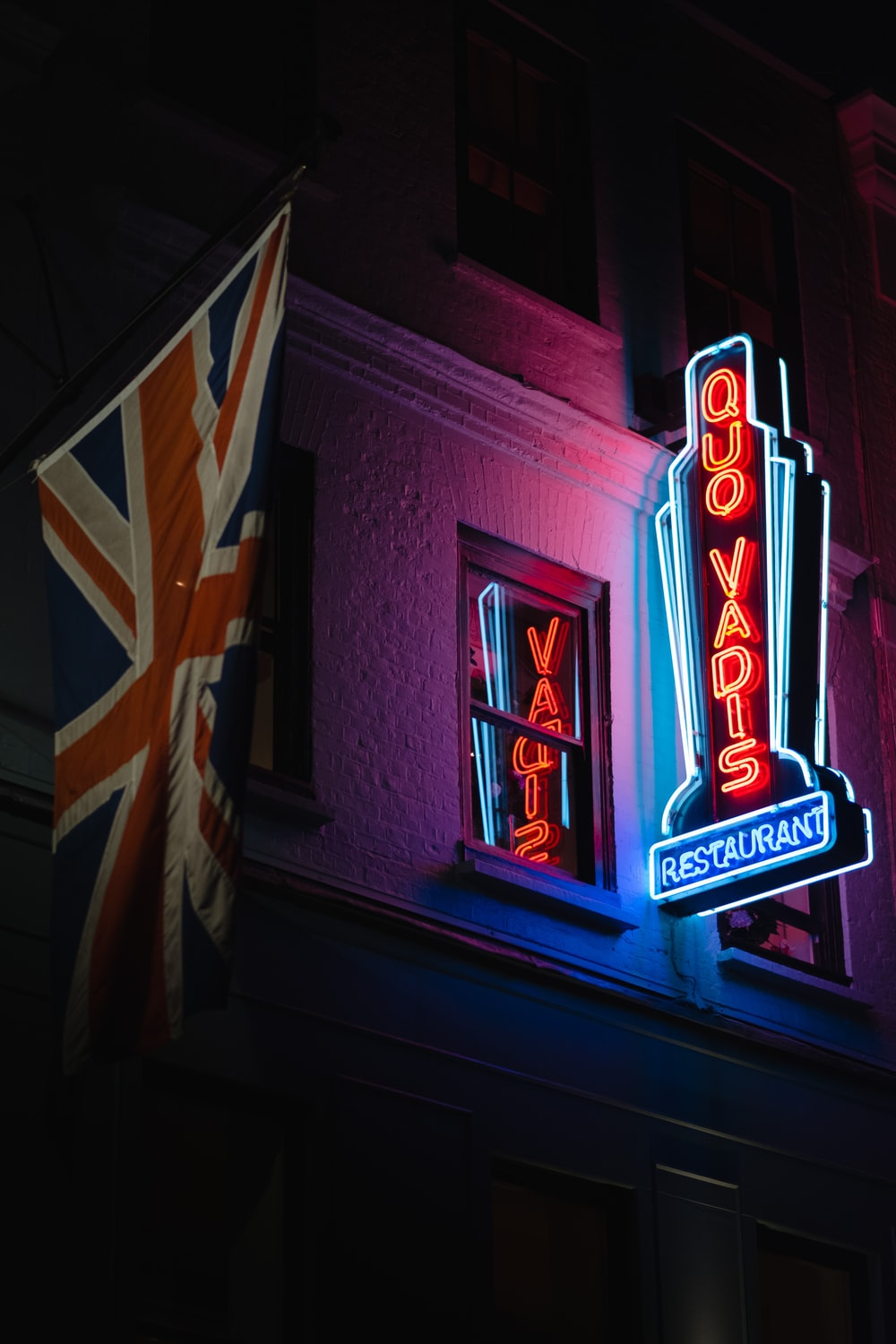 worm's eye view photography of Quo Vadis neon light signage