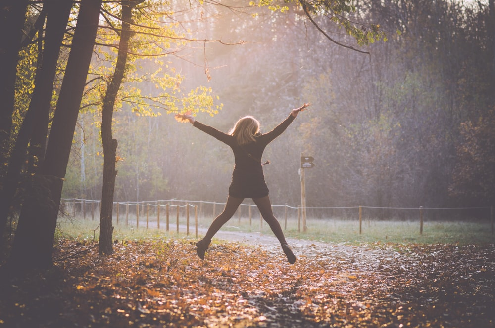 woman jumping under tree surrounded with dried leaves