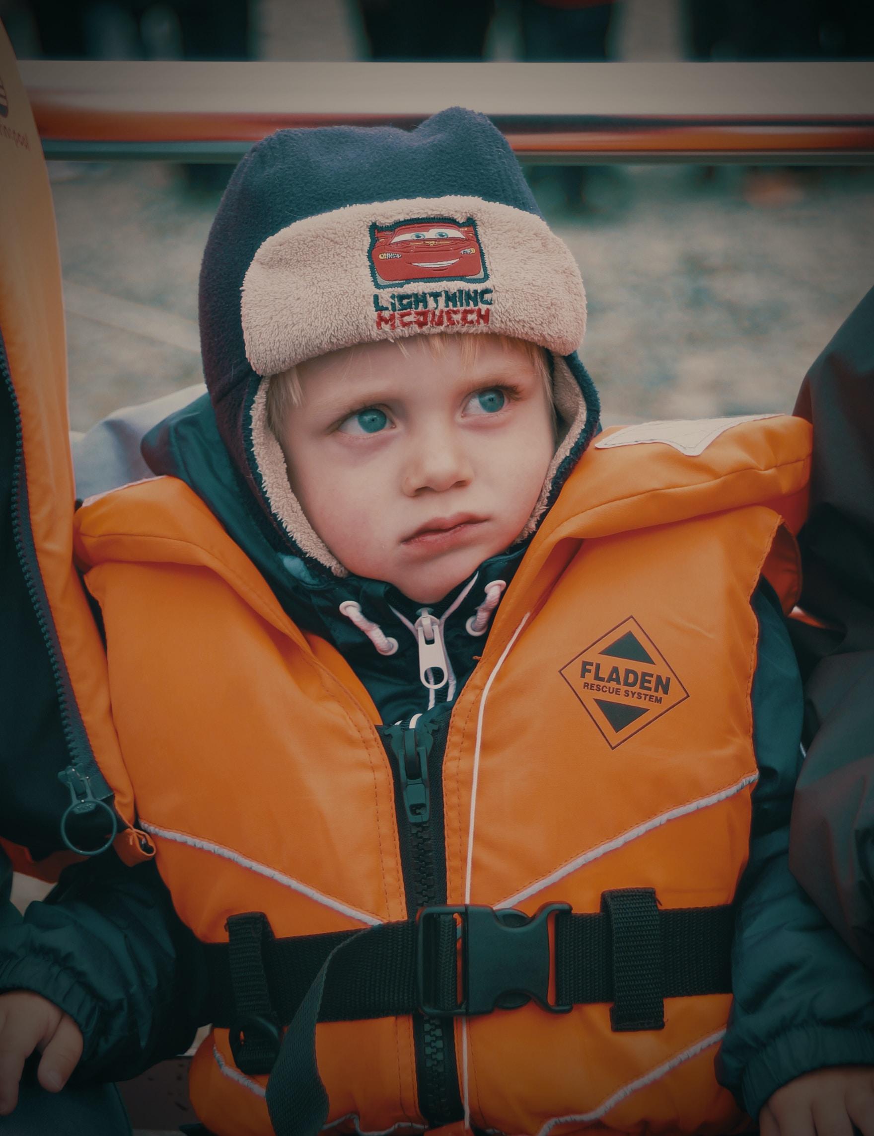 child wearing orange life vest