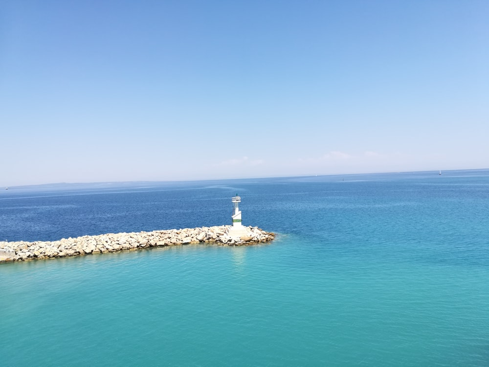 white lighthouse surrounded with body of water