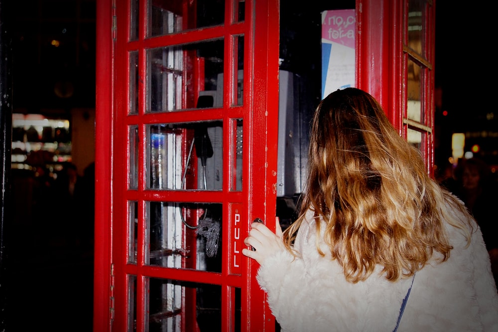 woman about to open the phone booth