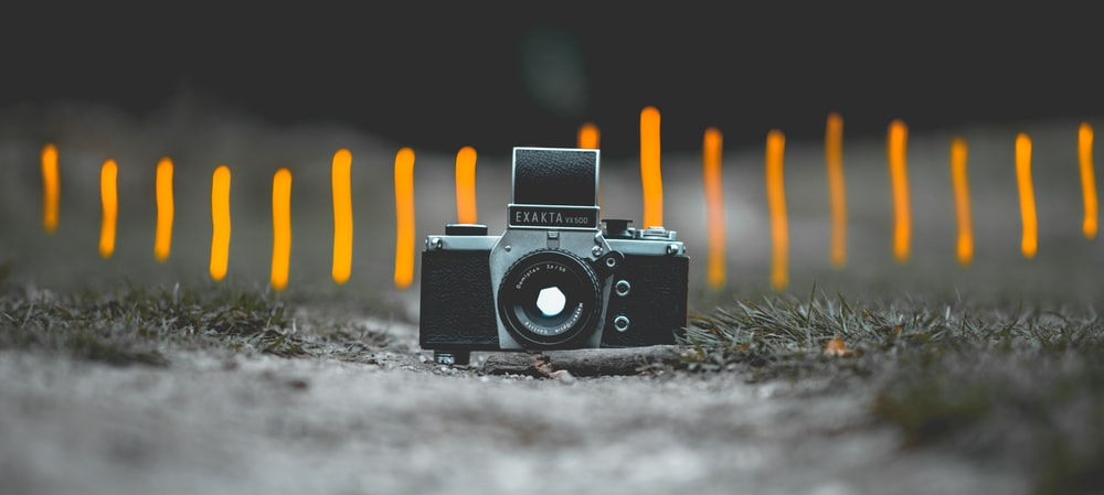 selective focus photography of black and gray SLR camera on gorund