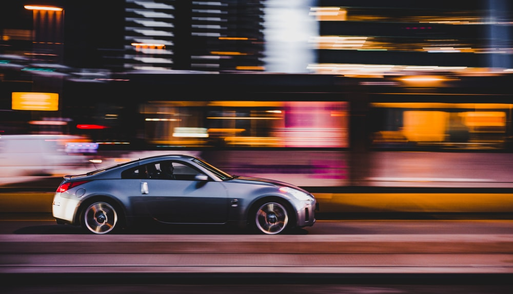 panning photography of gray coupe on road