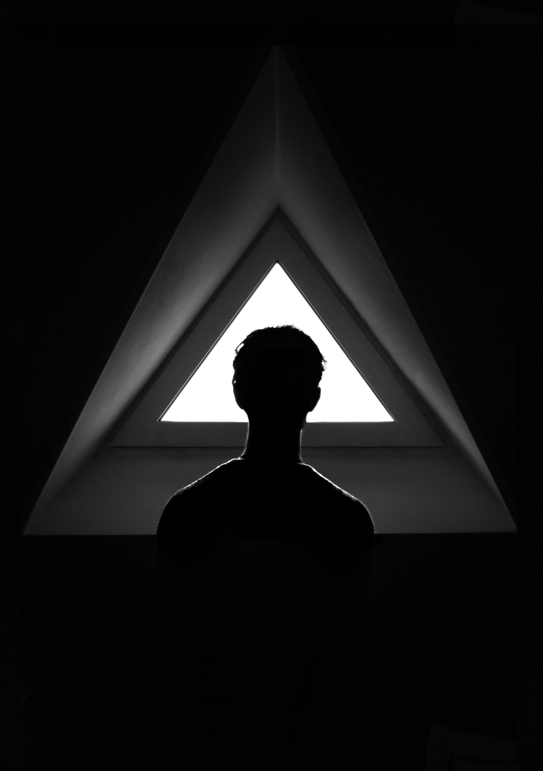 Man looks through triangular window.