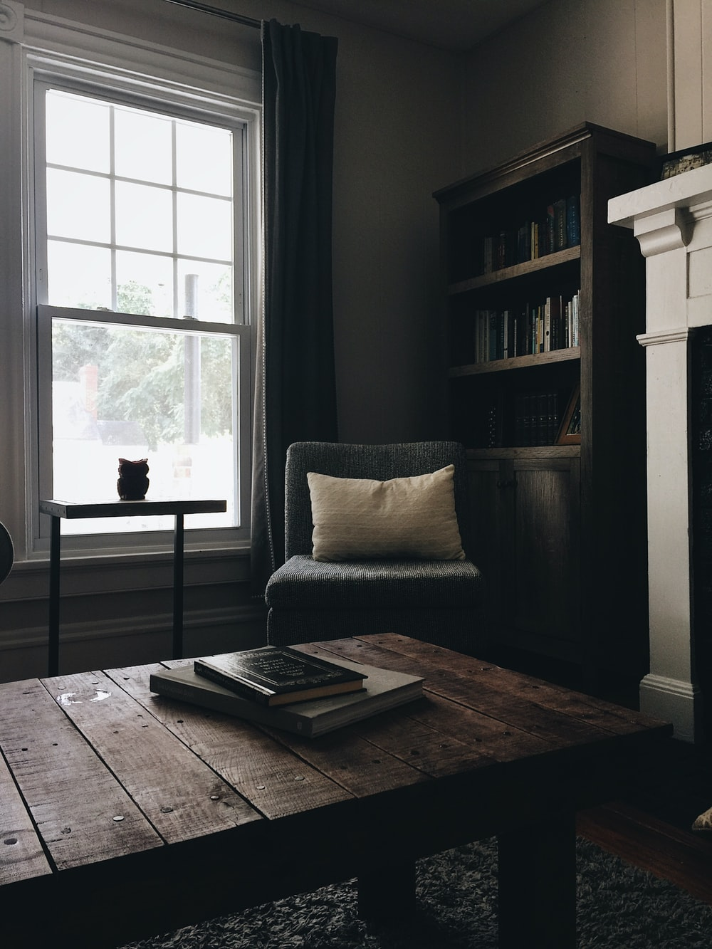 gray throw pillow on black chair by the window