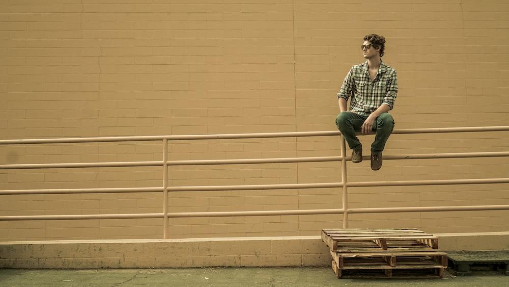 man sitting on white metal barricade