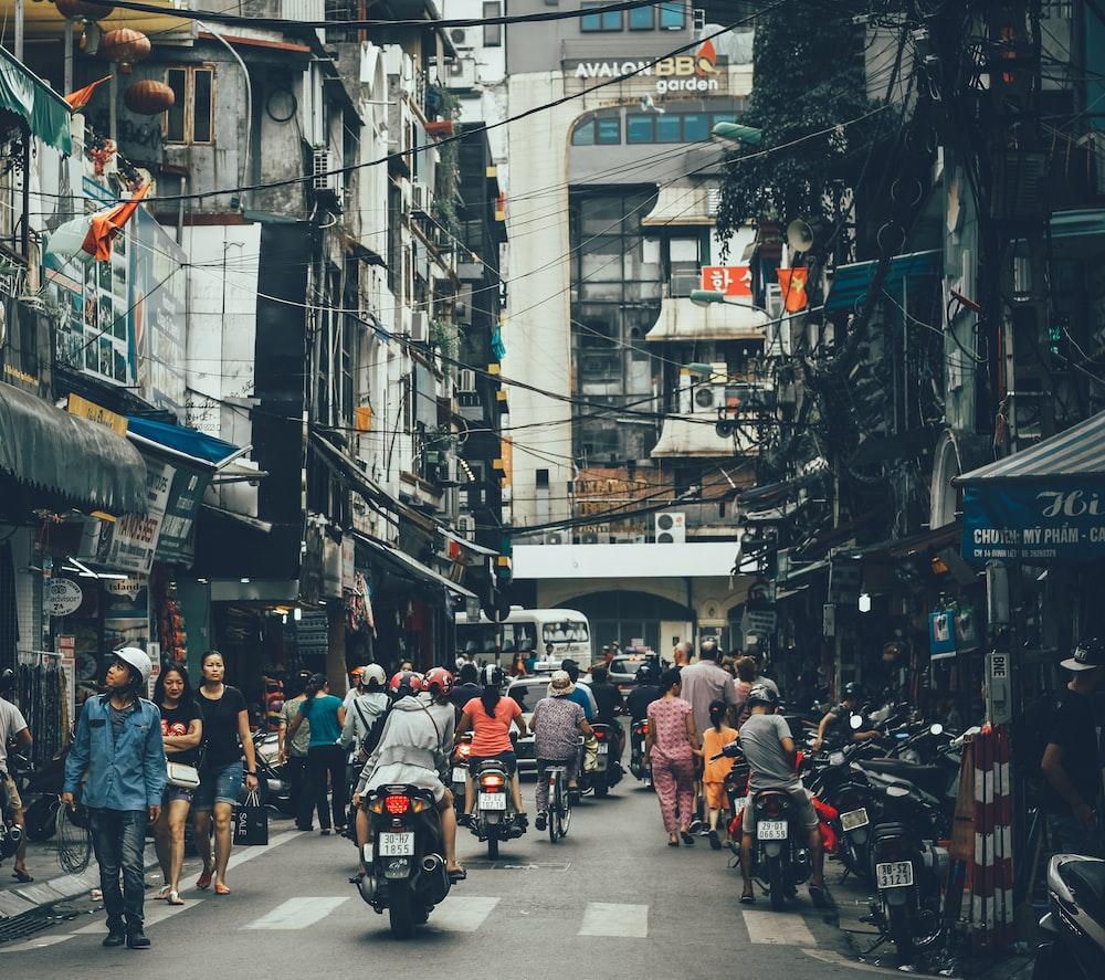 people walking on road between buildings