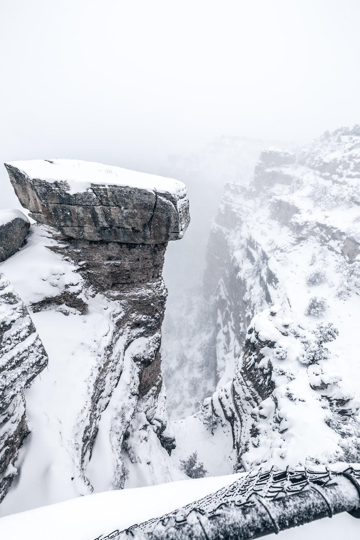 snowy cliff under foggy sky