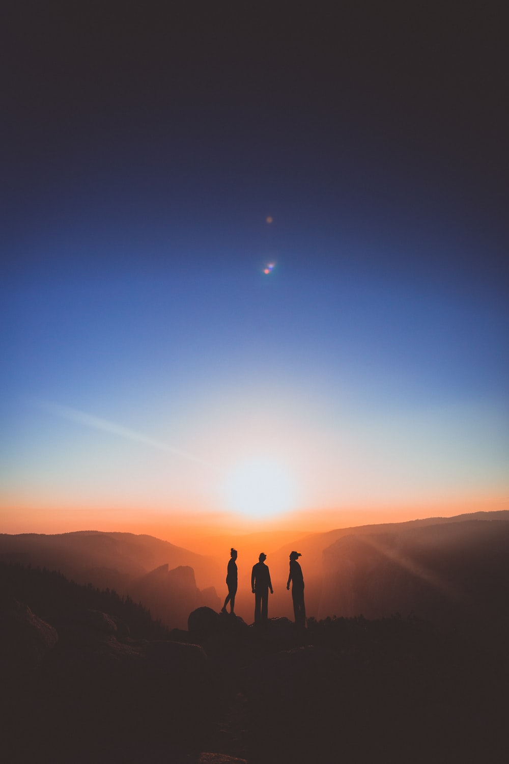 silhouette of three person standing on mountain