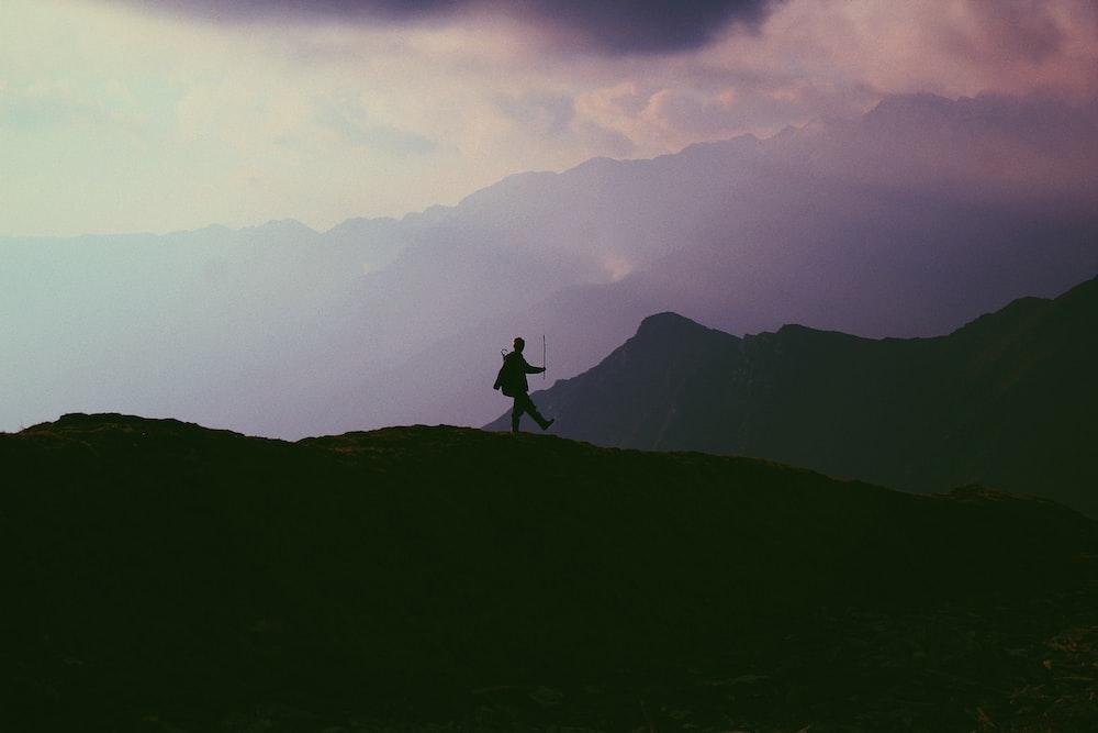 silhouette photo of person walking on mountain