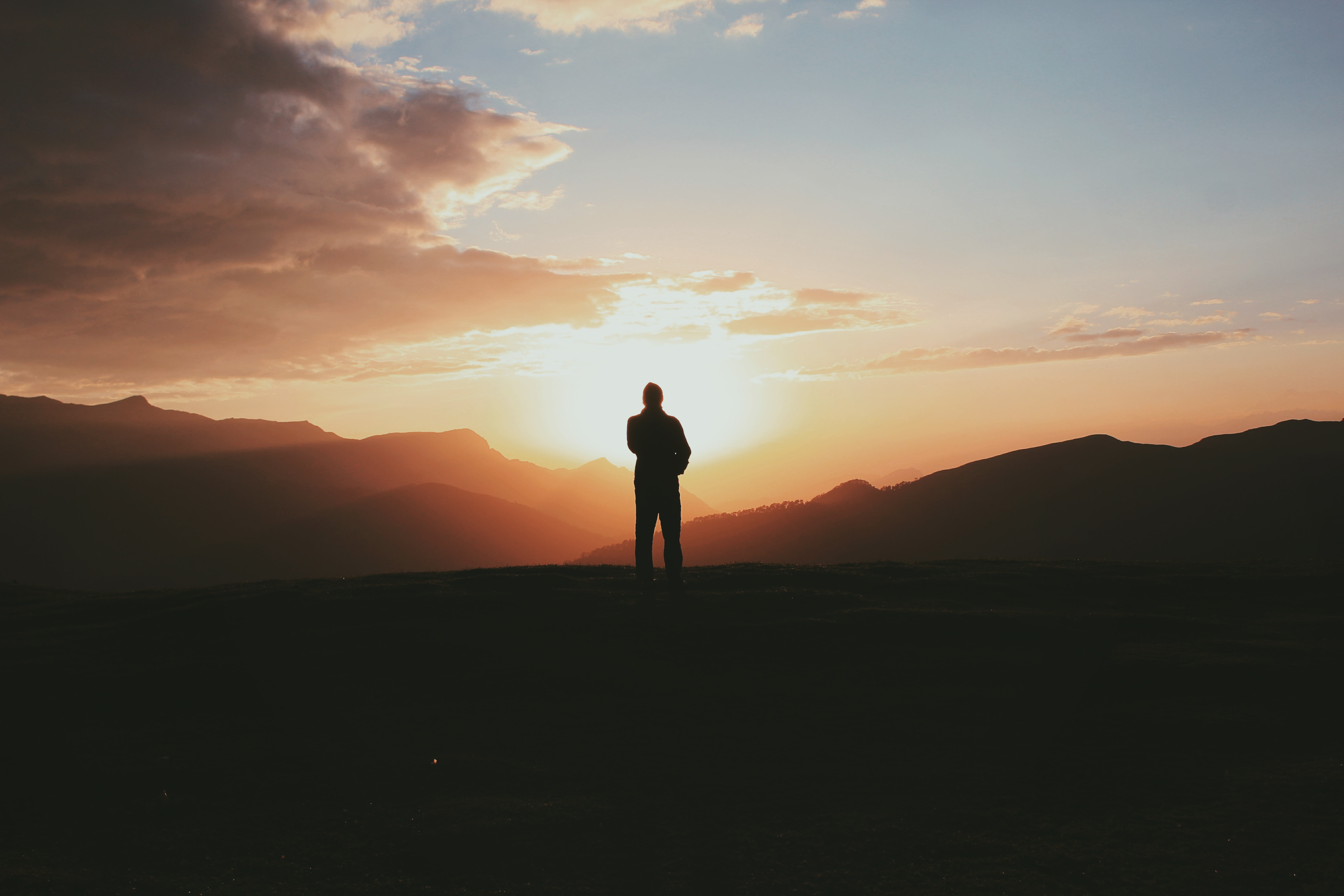 silhouette photo of man standing on mountain during golden hour