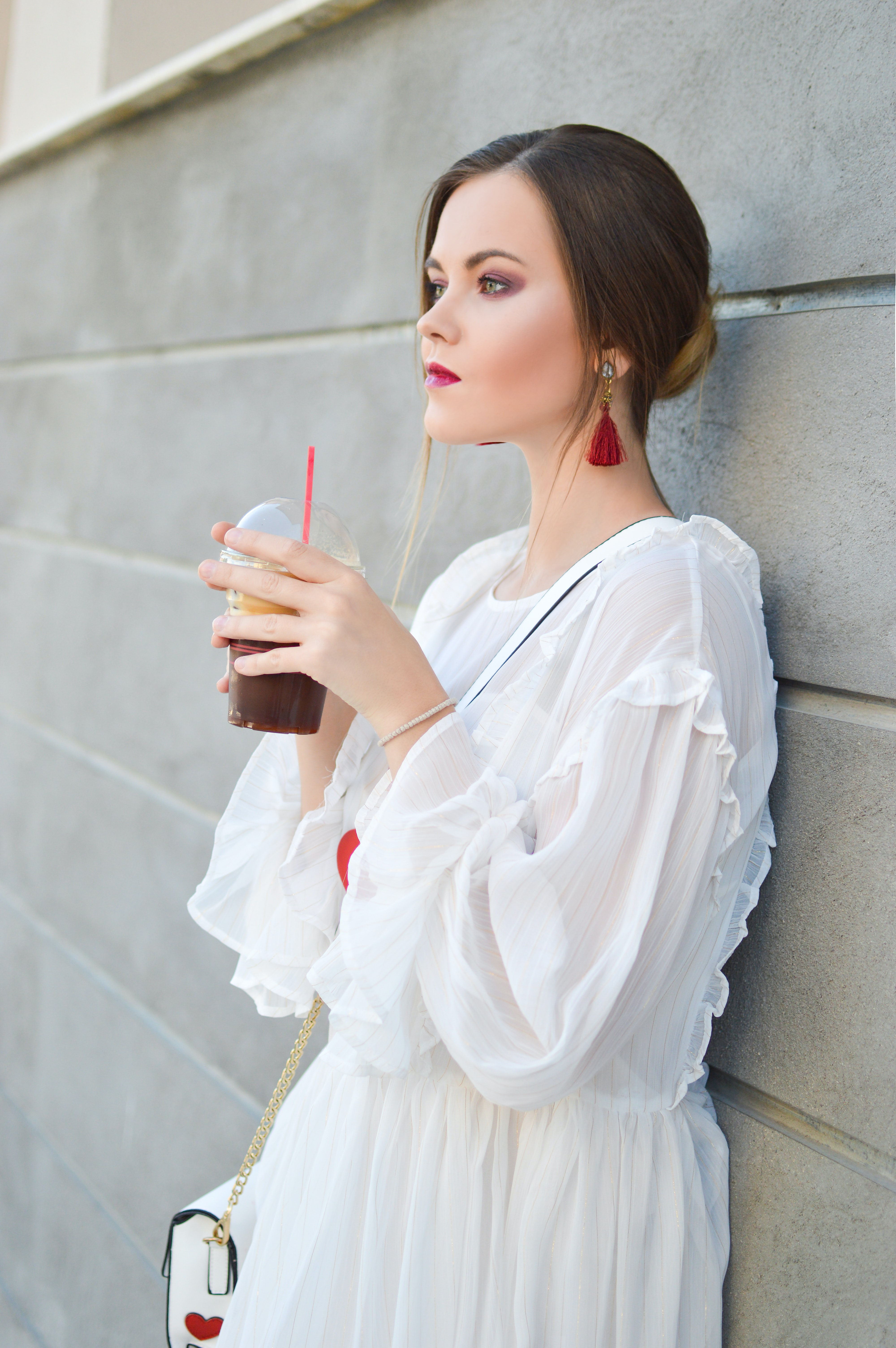 woman leaning on wall holding cups of black beverage