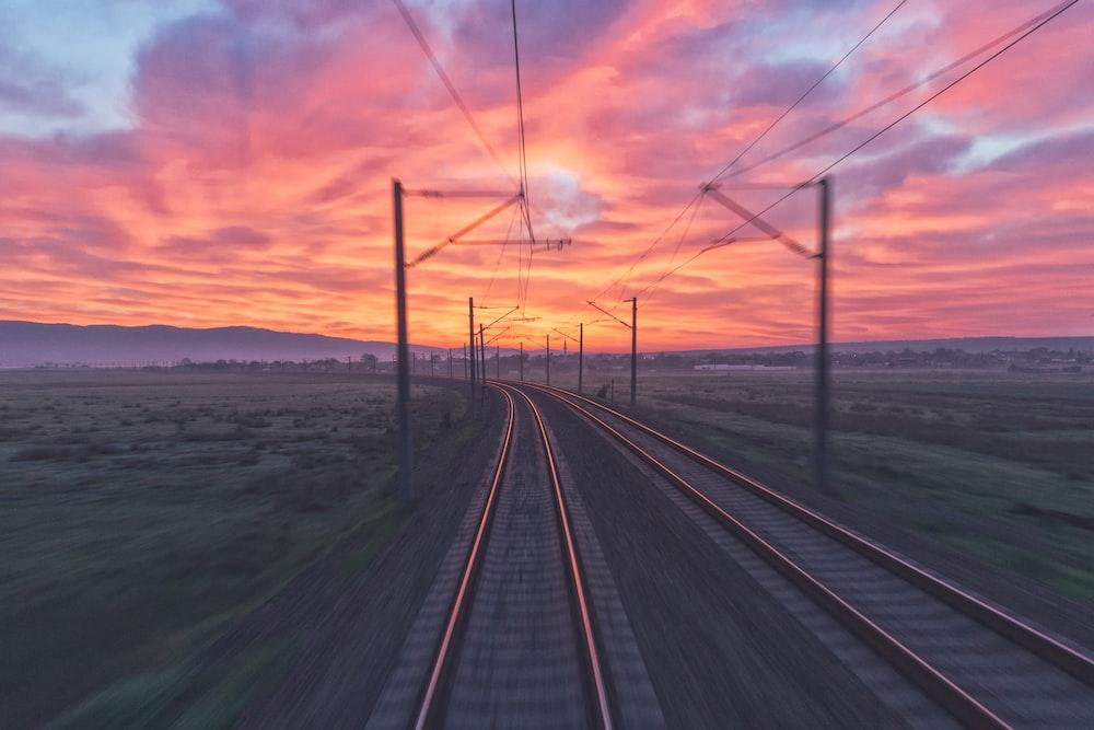 empty train tracks near green grass during sunset