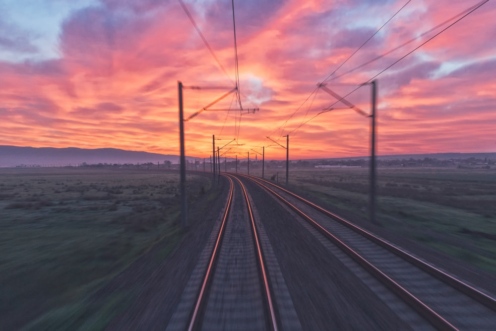 empty train tracks near green grass during sunset