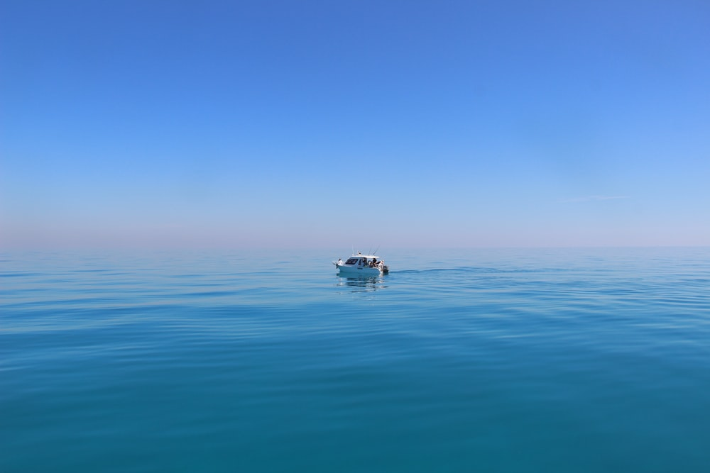 white boat under blue sky photography