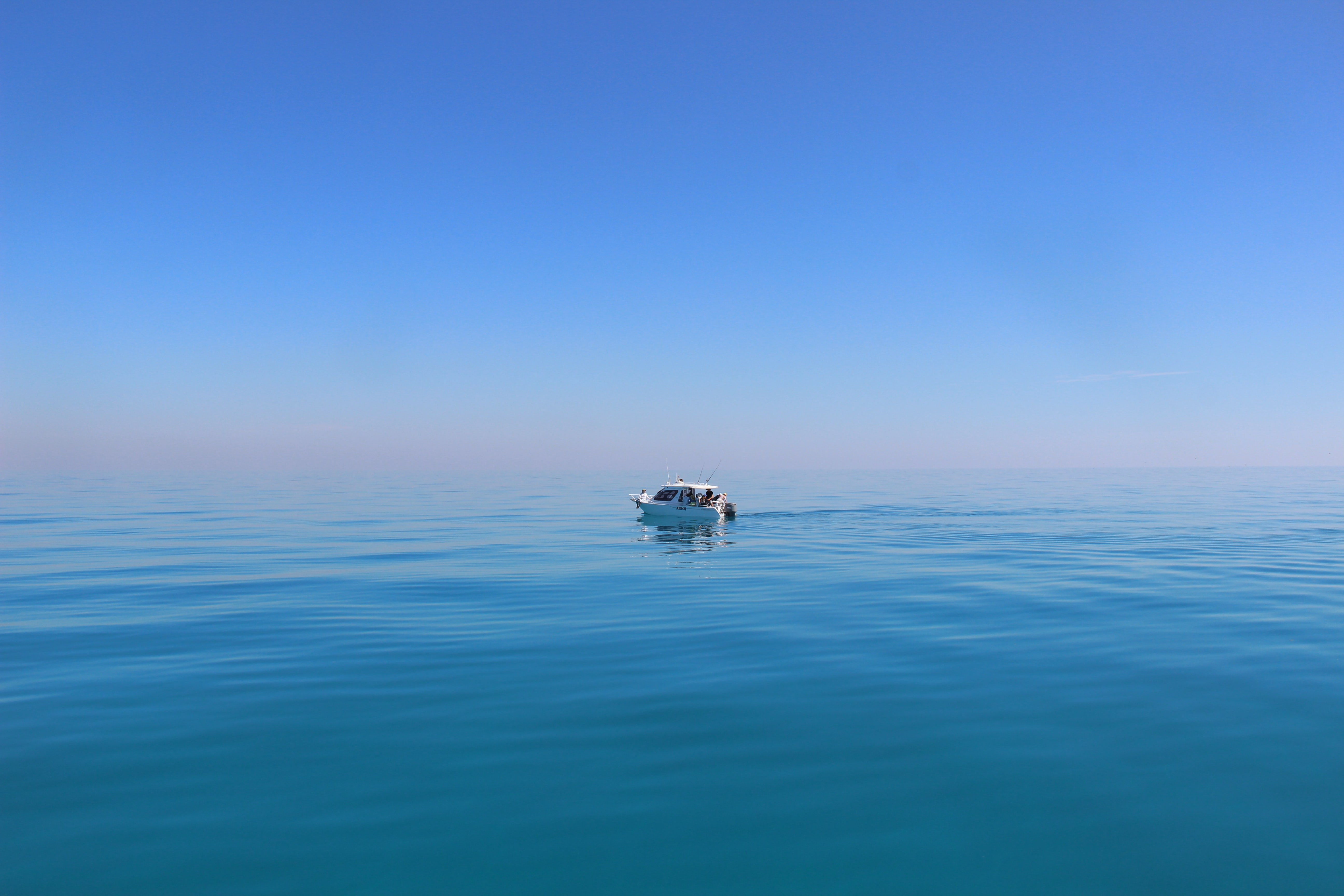 white boat under blue sky photography