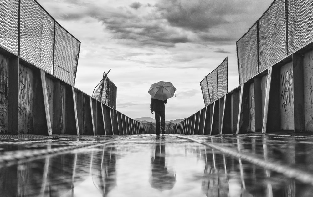 greyscale photo of person standing on pathway while holding umbrella
