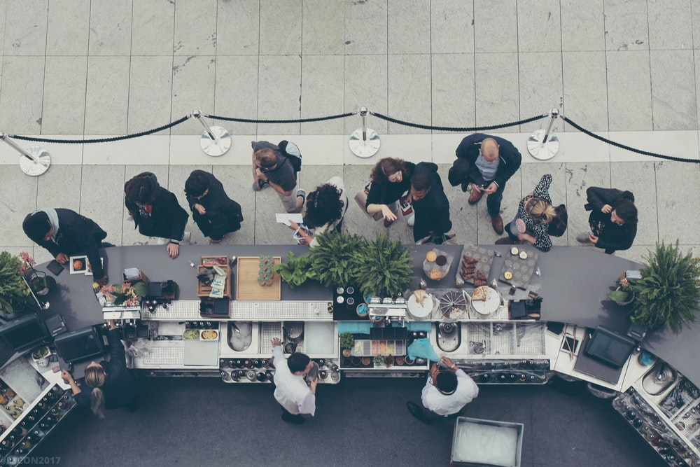aerial view photography of people lining-up at the food counter