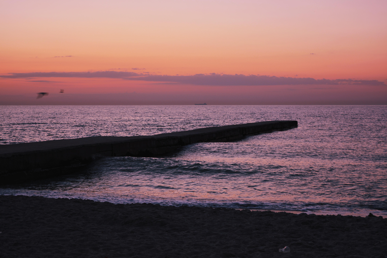 black concrete boardwalk on body of water