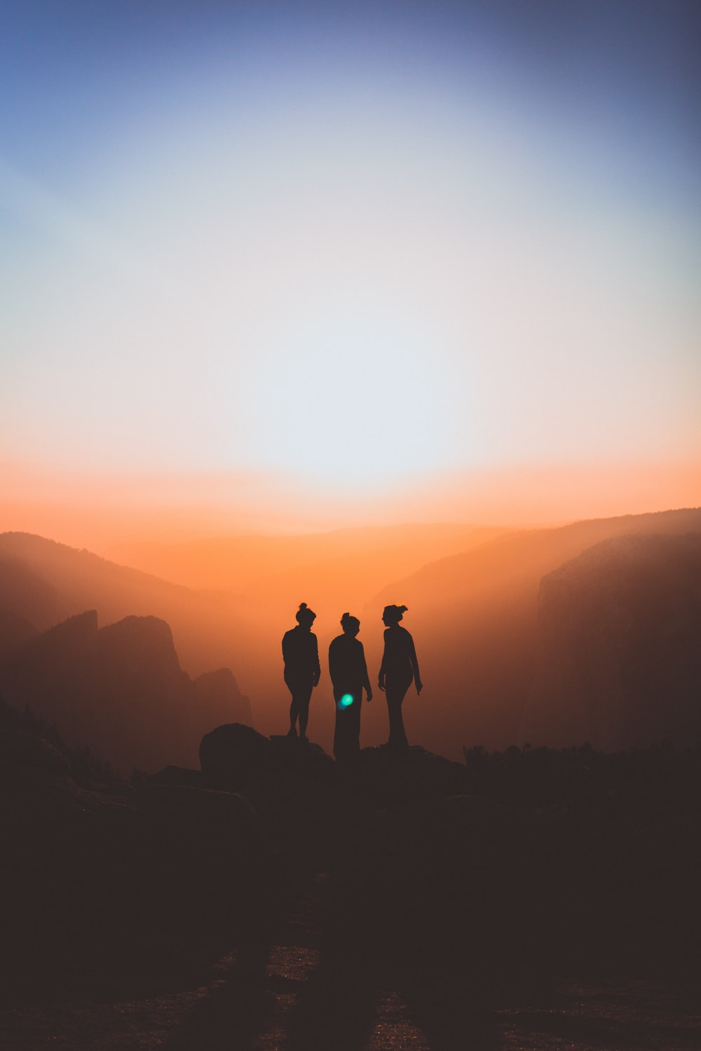 silhouette of three people up on mountain cliff
