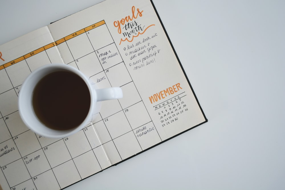 white ceramic mug with coffee on top of a planner